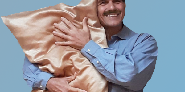Handsome guy with mustache hugging pillow
